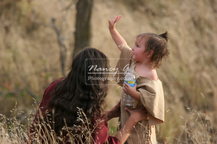 A Native American Indian mother and her daughter sitting outside having a picnic waving to friends