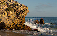 Waves crash into a wall of rock at the shoreline, seen from Corona Del Mar State Beach after having walked down to it from Inspiration Point.  Inspiration Point is just south/east of Corona Del Mar State Beach in Newport Beach, CA.