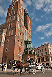 A horse carriage rides past St. Mary's Basilica in Krakow, Poland. St. Mary's Basilica sits on the Main Market Square which is the largest medieval square in Europe and dates back to the 13th century