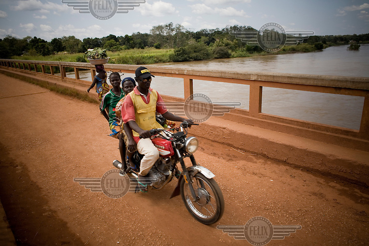 A man carrying two children on the back of his motorbike crosses a bridge over a wide river while a woman walks in the other direction carrying food in a bowl on her head.