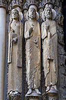 West Facade, Central Portal - Left Jamb Figures c. 1145. Cathedral of Chartres, France . Gothic statues on the left jamb of the central portal. All have haloes. The leftmost is a crowned woman whose hair is in long plaits; she holds a book. The central figure is a bearded man in a cap that resembles the ones worn by other jamb figures and by figures in the tympanum of the right portal. He holds an unidentified object. The figure nearest the portal is a bearded man holding a scroll and raising one hand- palm outwards- towards the viewer. A UNESCO World Heritage Site. .