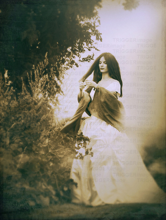 A sepia toned image of a woman in a white bridal gown, standing by a tree, touching her hair.