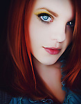 Retouched close up of young woman with red hair and blue eyes looking into camera