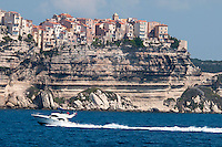 Bonifacio, Corsica, France, September 2012. The most vivid view of Bonifacio is from aboard a boat in the sapphire-blue Bouches de Bonifacio (Strait of Bonifacio). From the water, the tall, sun-bleached buildings of Bonifacio's citadel appear to morph seamlessly into the serrated white limestone cliffs rising up from the sea. Within the clifftop citadel is a charming maze of alleyways with a distinct medieval feel. A sheer 70m below, on the northern side, is Bonifacio's vibrant port, which spills over with café terraces and shops. Corsica is a wildly beautiful French island, scented with myrtle and possessing one of the most diverse landscapes in Europe, from crescent bays with white-sand beaches to montane forests sheltering rugged granite peaks, with miles of untouched coastline, sun-splashed mountain villages. Photo by Frits Meyst/Adventure4ever.com