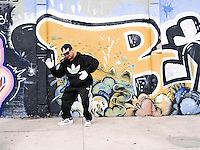 Street rapper dancing  near a graffited wall