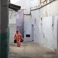 A woman walking in a narrow street in the medina or old town of Tetouan on the slopes of Jbel Dersa in the Rif Mountains of Northern Morocco. Tetouan was of particular importance in the Islamic period from the 8th century, when it served as the main point of contact between Morocco and Andalusia. After the Reconquest, the town was rebuilt by Andalusian refugees who had been expelled by the Spanish. The medina of Tetouan dates to the 16th century and was declared a UNESCO World Heritage Site in 1997. Picture by Manuel Cohen