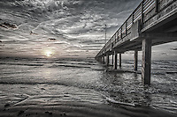 This is an almost black and white of a pier in Port A Texas as the sun was coming up over the water with great clouds and we loved the texture of the sand and surf that the BW created along with the wooden structure of the bridge.