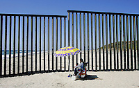 Beach-goers with the border wall in back in the Las Playas area of Tijuana, Mexico.  Since  the introduction of Operation Gatekeeper and the events of 9/11, security along the border has tightened along border cities such as San Diego, El Paso and other large cities causing migrants to cross from Mexico into the United States in more remote areas.  As a result, an ever increasing number of deaths have been reported and commerce has been severely affected.  2006 was also the year hundreds of thousand Latinos took to the streets across the United States in an effort to show Congress and the President how vital they are to America.