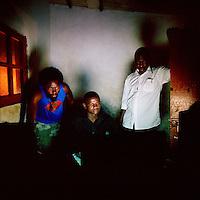 DJ NEL IT (Centre) with friends work late in his self-made recording studio in Sambizanga musseque (slum)..