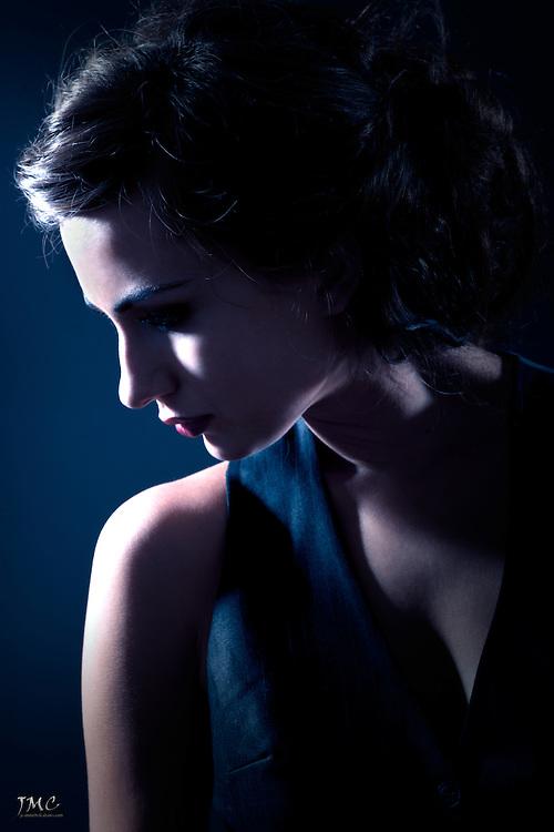 Dark portrait of young brunette women on blue background