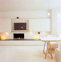 The white dining table and chairs are positioned in the bay window of the living room while the main wall supports a plasma screen behind sliding panels and a minimalist gas fire