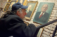 Visitor looks on paintings depicting Soviet leader Vladimir Ilyich Lenin. Large number of artifacts from Hungary's socialist past were found in the basements of different ministries after a change in political power. These communist pictures and sculptures are now being prepared for a charity auction to support those affected by the recent red sludge catastrophe in Hungary. The auction drawing great attention from around the world is to be held on December 6th in Budapest, Hungary. Photos taken during preparations for the auction on November 25, 2010. ATTILA VOLGYI