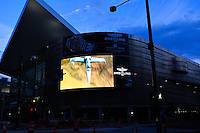 Video advertising billboard on the exterior of the Colorado Convention Center in downtown Denver at dusk.