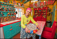 BNPS.co.uk (01202 558833)<br /> Pic: PhilYeomans/BNPS<br /> <br /> Artist Mary Rose Young in the kitchen.<br /> <br /> Britain's wackiest property has come on the market...And the estate agents mantra of paint everything magnolia has definately not been applied.<br /> <br /> It may look like an idyllic cottage in the Forest of Dean from the outside but ceramic artist Mary Rose Young's unique taste has transformed the interior into what looks like something from Alice in Wonderland.<br /> <br /> The three-bedroomed house is decorated from head to toe in crazy colours, clashing patterns, and enormous murals,<br /> each room is covered in the garish designs, including the bathroom, where even the sink and toilet have been adorned in bright tiles.<br /> <br /> Estate agents Bidmead Cook now have the tricky task of showing prospective punters round the &pound;500,000 property.