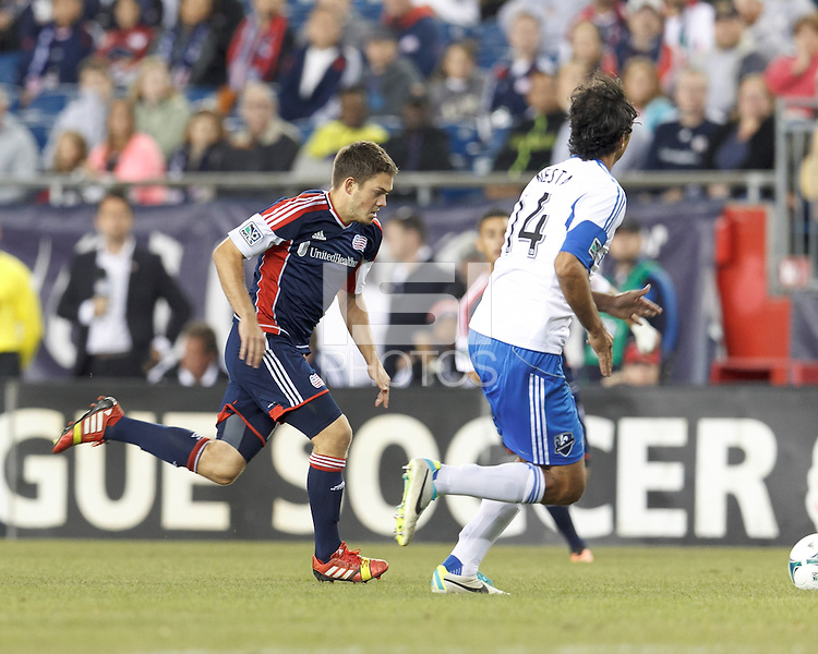New England Revolution midfielder Kelyn Rowe (11) brings the ball forward.  In a Major League Soccer (MLS) match, Montreal Impact (white/blue) defeated the New England Revolution (dark blue), 4-2, at Gillette Stadium on September 8, 2013.