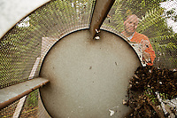 E'Ton Littlepage turns the crank on the compost screener. The screener, built by the prison maintainence department out of an old clothing dryer, filters out the trash and wood chips that did not break down and drops the pure filtered compost on the ground below.