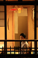 A woman in kimono is seen through a window in Gion neighborhood at night in Kyoto, Japan, on November 7, 2006. Kyoto is the former imperial capital of Japan, and today houses more than 1.5 million. Photo by Lucas Schifres/Pictobank