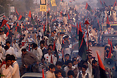 Rawalpindi, Pakistan<br /> November 10, 1988<br /> <br /> Crowds greet Benazir Bhutto as she arrives at a campaigns rally in Rawalpindi.<br /> <br /> Benazir Bhutto is the eldest child of former Pakistan President and Prime Minister Zulfikar Ali Bhutto. She found herself placed under house arrest in the wake of her father's imprisonment and subsequent execution in 1979. In 1984 she became the leader in exile of the Pakistan Peoples Party (PPP), her father's party, though she was unable to make her political presence felt in Pakistan until after the death of General Muhammad Zia-ul-Haq. <br /> <br /> On 16 November 1988 Benazir's PPP won the largest bloc of seats in the National Assembly. Bhutto was sworn in as Prime Minister in December, at age 35 she became the first woman to head the government of a Muslim-majority state in modern times. <br /> <br /> She was removed from office 20 months later under orders of then-president Ghulam Ishaq Khan for alleged corruption. Bhutto was re-elected in 1993 but was again removed by President Farooq Leghari in 1996, on similar charges. Bhutto went into self-imposed exile in Dubai in 1998, until she returned to Pakistan on October 2007, after General Musharraf granted her amnesty and all corruption charges withdrawn.