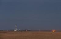 A drill rig and natural gas flares near Ray, North Dakota.