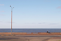 Coast line at dawn. Empty street. Lamp post with one person sitting on a bench. all alone. Montevideo, Uruguay, South America