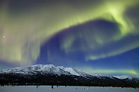 Aurora borealis swirls across the sky over the Brooks mountain range, arctic Alaska.