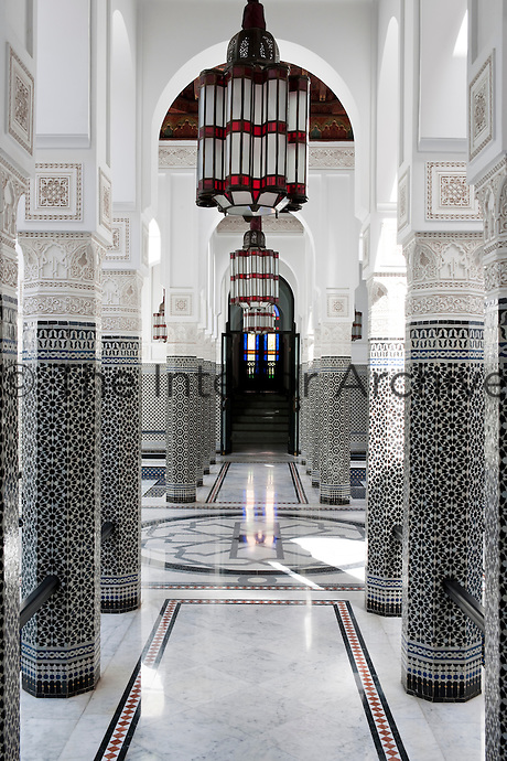 The columned courtyard with black and white mosaic tiles, and glass lanterns leading the view to the stained glass door