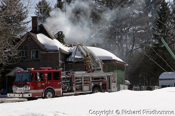 A ladder truck at the scene of a house fire