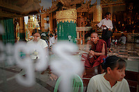 People are seen behind a box with donations at the Shwedagon pagoda in Yangon April 3, 2012. Myanmar President Thein Sein said on Tuesday the country's by-elections at the weekend, which were swept by the opposition, were carried out successfully.  REUTERS/Damir Sagolj (MYANMAR)