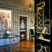 The ivory inlaid black lacquer doors feature geometric architectural images