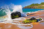 Surf crashing on lava rocks at Secret Beach (Kauapea Beach), Kilauea Lighthouse visible, Kauai, Hawaii USA