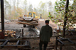 Seldon Back, 75, watches as the bulldozer hauls away the bark logs recently cut at Clarence Bailey's Saw Mill in Breathitt, KY.