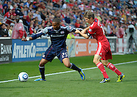 Chicago midfielder Logan Pause (12) pressures New England defender Darrius Barnes (25).  The Chicago Fire defeated the New England Revolution 3-2 at Toyota Park in Bridgeview, IL on Sept. 25, 2011.