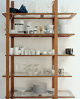 Detail of a simple wood and glass shelving unit in the kitchen housing glassware and white crockery