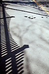 The shadow of a wooden fence on a road, CT, USA