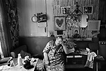 Older womanin her living room Peabody Estate flat tenement building Tower Hamlets east London UK 1975