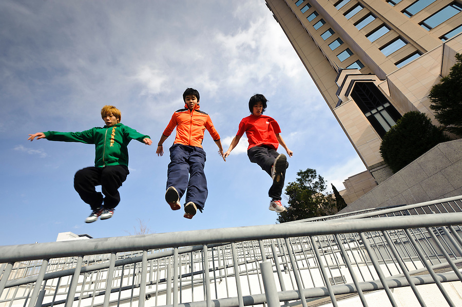 """(L to R) Traceurs (Parkour practitioners) """"Zen"""", Jun """"Sullivan"""" Sato, and """"Yutaro"""". Practicing Parkour in Odaiba, Tokyo, Japan, January 27, 2012. Parkour is a modern method of physical training, also known as freerunning. It was founded in France in the 1990s. There is a small group of around 50 parkour practitioners in Tokyo."""