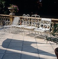 Four white-painted wrought-iron garden chairs stand in a row on this sun-filled balustraded terrace