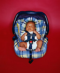 Baby boy (6-9 months) sleeping in carseat, overhead view