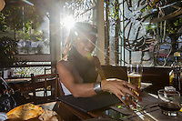 Rio de Janeiro lifestyle - sun-bleached scene of young beautiful woman have a chope ( draught beer ) in a Rio de Janeiro restaurant, Brazil. Draught beer, also spelt draft, is beer served from a cask or keg rather than from a bottle or can. Canned draught is beer served from a pressurised container containing a widget.