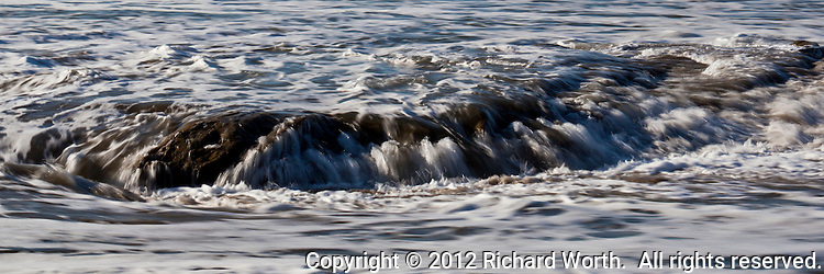 A wave washes over and scrubs an outcrop of rock on Pomponio State Beach creating broad,  painterly strokes of white and shades of brown.