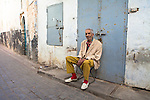 An old muslim man, with an eye for fashion, sitting on a chair in an alley of the old medina of Salé, near Rabat, Morocco. Model released.