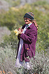 Woman picking wild flowers in Biedouw Valley in spring, Cedarberg, Western cape, South Africa