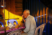 An old man having his cup of Tea in the morning in the streets of Phnom Penh, Cambodia