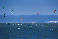 Kite surfing on San Francisco Bay with the colorful kites floating over the San Mateo Bridge as viewed from Crown Beach in Alameda, California.