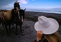 Members of the rodeo court at the Curry County Fair in Gold Beach, Oregon, stop to recover a hat that was blown off during the court's victory lap on the beach. The victory lap takes place at the end of the parade.