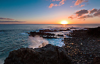 Sunset reflects over the waters off a rocky beach in Makaha, O'ahu.