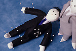Voodoo doll lying on blue backdrop dressed as a business man in a black suit and blue tie with pins stuck in his body with another voodoo doll in grey suit standing over him
