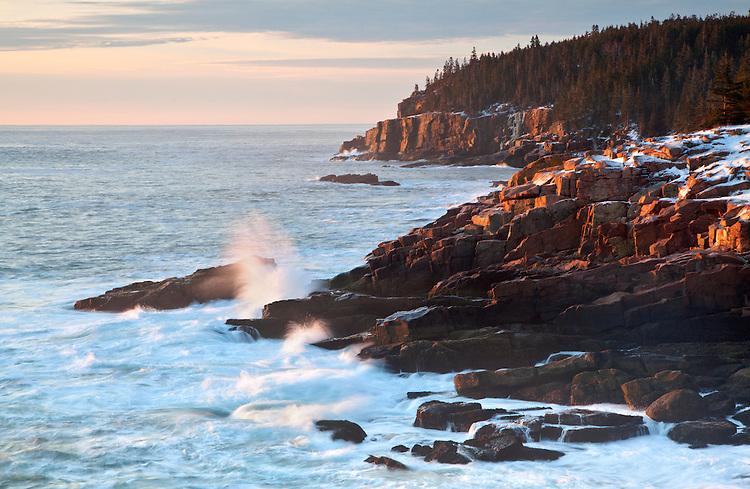 Morning sun illuminates the Otter Cliff and the rocky shoreline along Ocean Drive in Acadia National Park, Maine, USA