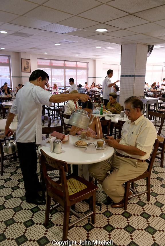 Waiter pouring hot milk from a kettle into a customer's cafe con leche at the Gran Cafe de la Parroquia, Veracruz city, Mexico