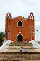 Two Mexican school children in front of the Spanish colonial church in Santa Elena, Yucatan, Mexico